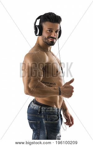 Handsome shirtless muscular bodybuilder man listening to music with headphones, isolated on white background, while doing thumb up sign with one hand