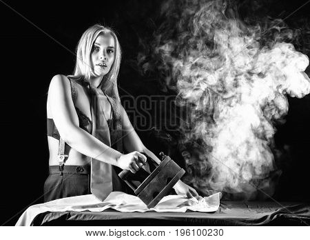 sexy blonde woman in men's pants and a bra, ironing white shirt with old iron. retro style, black and white.