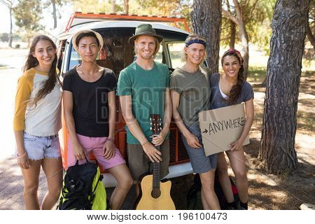 Portrait of friends with sign board standing by camper van on field