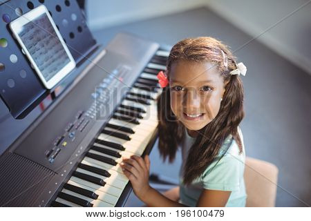Portrait of elementary girl practicing piano in class at school