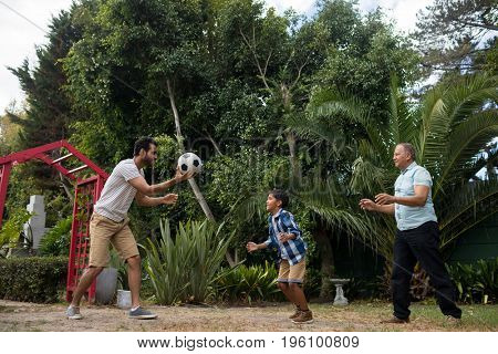 Happy family playing soccer against plant at park