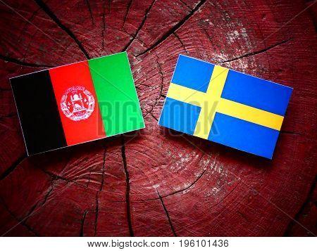 Afghani Flag With Swedish Flag On A Tree Stump Isolated