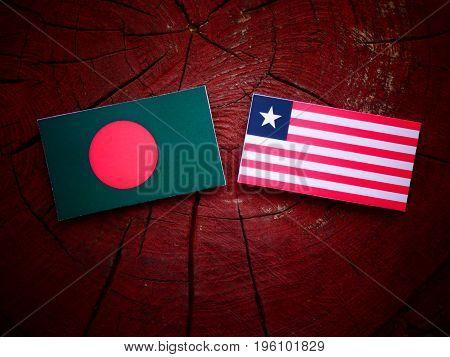 Bangladesh Flag With Liberian Flag On A Tree Stump Isolated