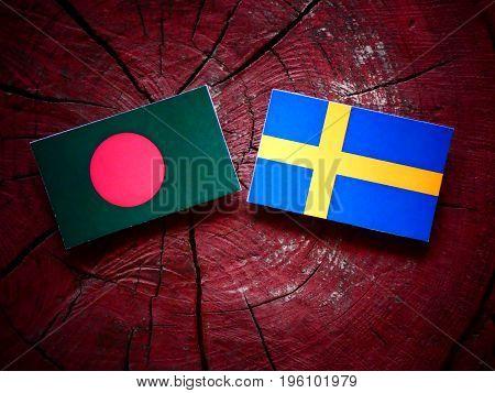 Bangladesh Flag With Swedish Flag On A Tree Stump Isolated