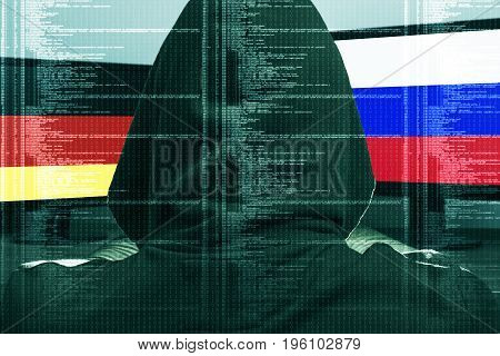 Hacker working on a cyber attack on Germany and Russia. Concept of hacking into the computer. Ger and Rus flag on the screen. German and Russian flag on the screen.