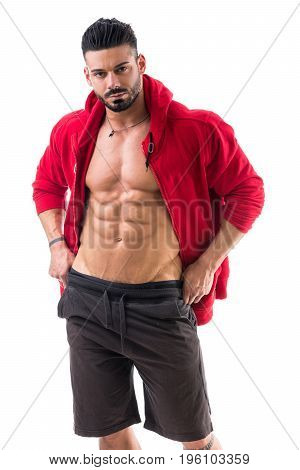 Muscular bodybuilder undressing, opening red hoodie sweater on naked muscle torso on light background