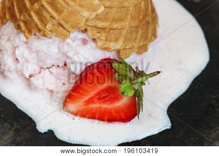 Strawberry Ice Cream In A Waffle Cone Inverted And Melted Against A Dark Background, Close-up