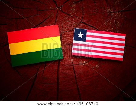 Bolivian Flag With Liberian Flag On A Tree Stump Isolated