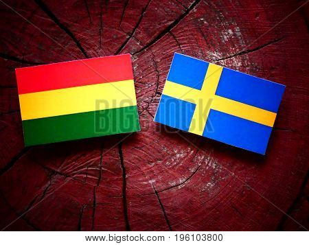 Bolivian Flag With Swedish Flag On A Tree Stump Isolated