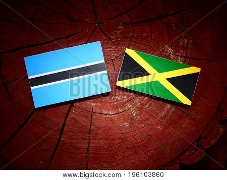Botswana Flag With Jamaican Flag On A Tree Stump Isolated