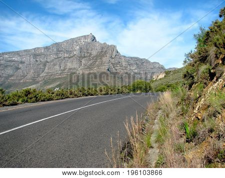 FROM CAPE TOWN, SOUTH AFRICA, WITH A ROAD IN THE FORE GROUND AND TABLE MOUNTAIN IN THE BACK GROUND