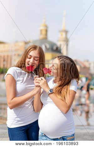 Lesbians mothers, pregnant couple, happy samesex family in the city park at summer. Women eating sweets, heart shaped candies, symbol of love