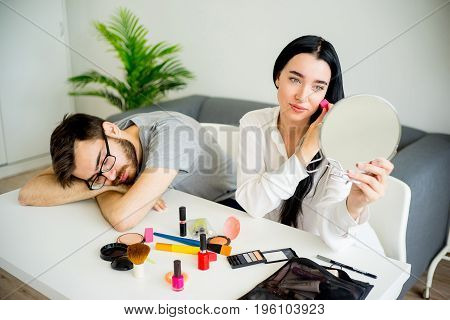 Bored husband waiting for wife while she is getting ready
