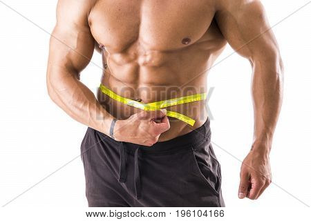 Muscular bodybuilder man measuring belly and hips with tape measure, close-up isolated on white background.