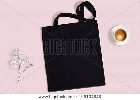 Black blank cotton eco tote bag with baby breath flower and cup of coffee on a pink background design mockup.