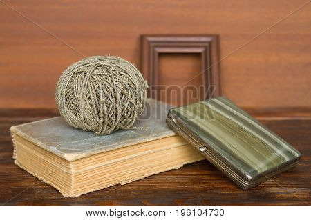 An old book a thread and a cigarette case on an old wooden table. Still life vintage