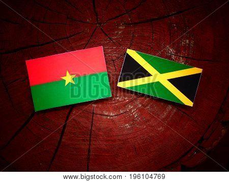 Burkina Faso Flag With Jamaican Flag On A Tree Stump Isolated