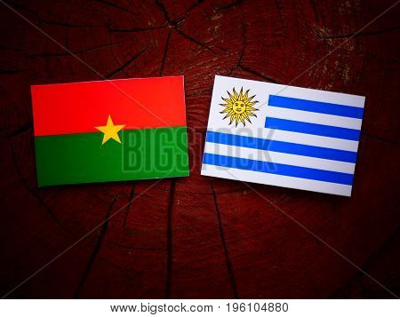 Burkina Faso Flag With Uruguaian Flag On A Tree Stump Isolated