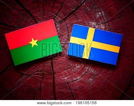 Burkina Faso Flag With Swedish Flag On A Tree Stump Isolated