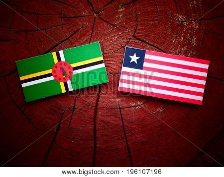 Dominica Flag With Liberian Flag On A Tree Stump Isolated
