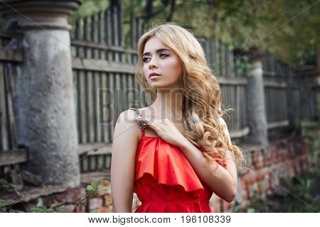 Outdoor fashion beautiful young woman photo near old HOMESTEAD summer. Portrait girl blondes in red dress