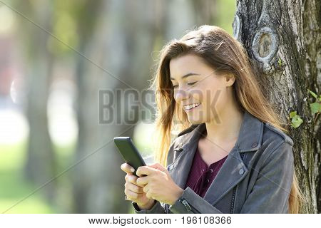 Happy single teen using a smart phone leaning on a tree outdoors in a park