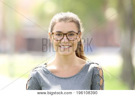 Portrait of a girl wearing eyeglasses looking at you outdoors in a park