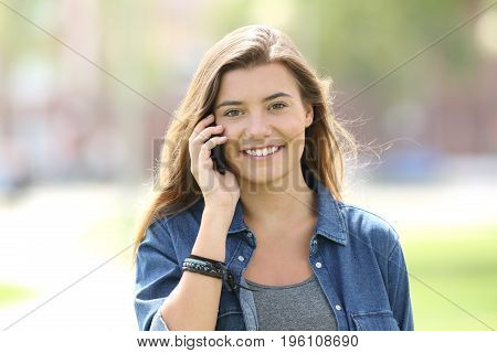 Front view of a single teen girl walking towards camera and calling on phone looking at you in the street
