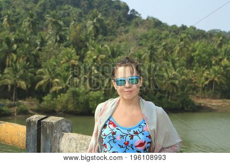 Beautuful girl posing on the brige near tropical forest