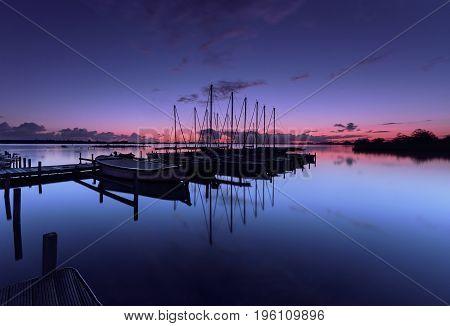 Sailboats at a platform in a calm lake at dawn