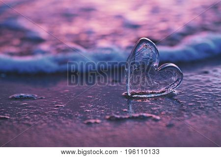 clear glass heart on  sand beach with sunrise sun light, Canary island, Spain