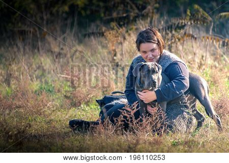 Girl and her gray dog in the field
