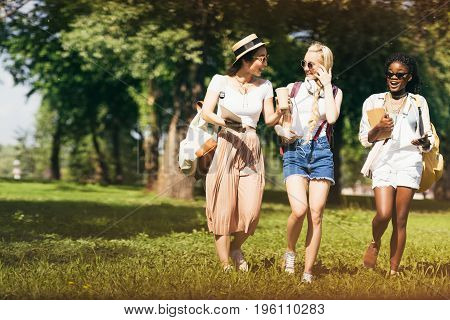 Cheerful Attractive Multiethnic Girls In Sunglasses Holding Textbooks While Walking In Park