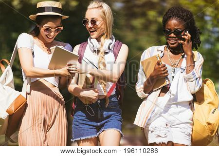 Cheerful Young Multiethnic Students Holding Books And Digital Devices While Talking And Walking In P