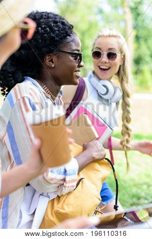 smiling young multiethnic students holding books and paper cup while talking in park