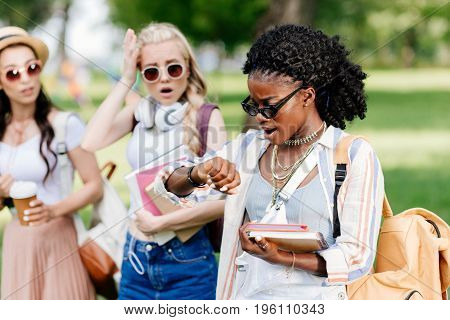 Young African American Woman In Sunglasses Holding Books And Checking Wristwatch While Emotional Gir