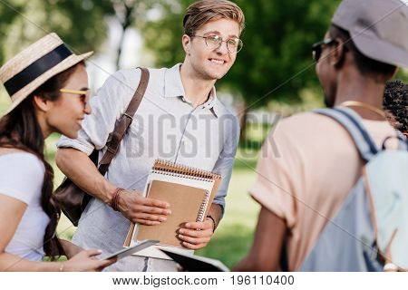 happy multiethnic students holding notebooks and talking in park