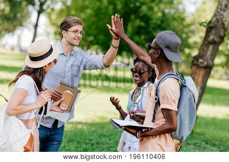 Cheerful Young Multiethnic Students Giving High Five While Standing Together In Park