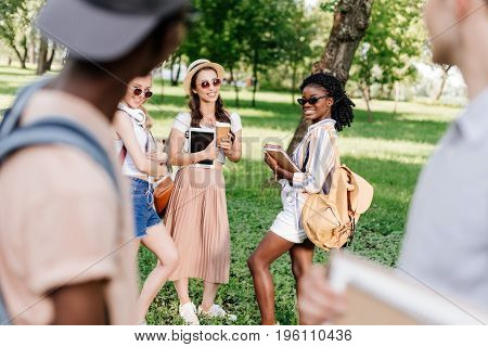 Attractive Smiling Girls In Sunglasses Holding Books And Digital Tablet While Looking At Boys In For