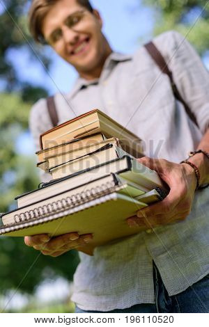 Close-up View Of Smiling Young Student Holding Pile Of Books