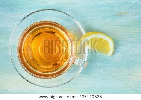 An overhead photo of a cup of vibrant tea with a slice of lemon, shot from above on a teal blue texture, with a place for text