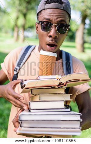 Young African American Man In Cap And Sunglasses Holding Pile Of Book With Paper Cup