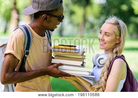 Side View Of Happy Young Multiethnic Couple Holding Books Together While Standing In Park