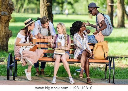 Cheerful Young Multiethnic Students Holding Books And Paper Cups While Sitting On Bench And Talking