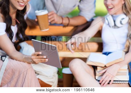 cheerful young students using digital tablet while sitting together on bench in park