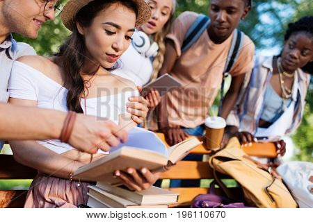 Young Multiethnic Students Reading Books Together On Bench In Park