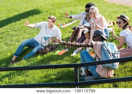 Cheerful Multiethnic Students Resting Together On Green Grass In Park