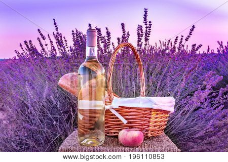 A photo of a bottle of white wine, a peach, and a picnic basket with a loaf of bread in a lavender field. Toned image