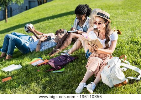 multiethnic group of students studying and resting on green grass in park