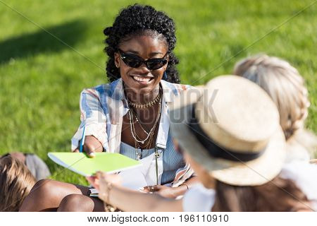 Smiling Young African American Woman In Sunglasses Giving Textbook To Classmates While Sitting On Gr
